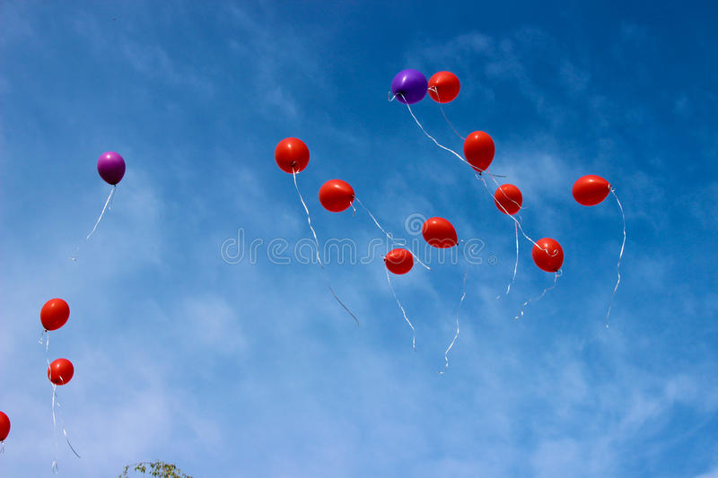 Balloons. Flight of balloons in the blue sky royalty free stock photos