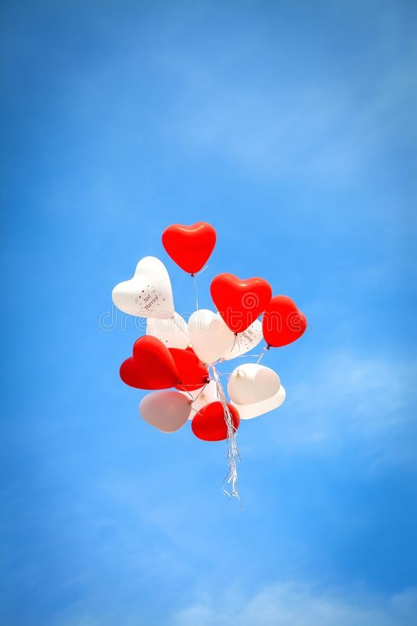 Red white balloons in the blue  sky on wedding day stock photo