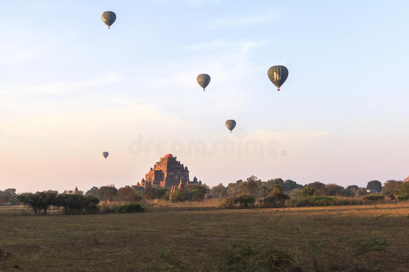 Balloons over Bagan at sunrise with horses royalty free stock image