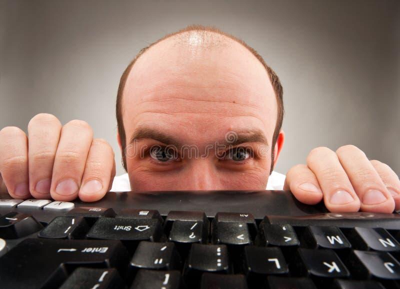 Ballot timide se cachant sous le clavier d'ordinateur photo stock
