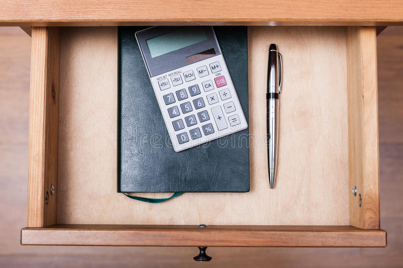 Ballpen, calculator and notebook in open drawer. Above view of ballpen, calculator and notebook in open drawer of nightstand royalty free stock images