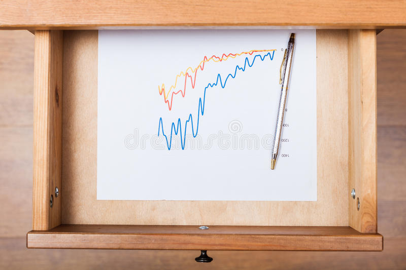 Ballpen on diagram in open drawer. Top view of ballpen on diagram in open drawer of nightstand royalty free stock photos