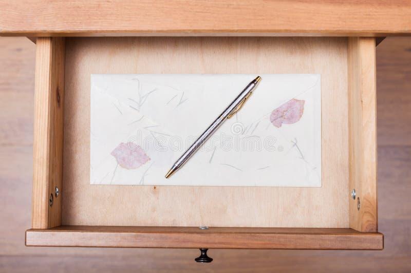 Ballpen on vintage envelope in open drawer. Above view of ballpen on vintage envelope in open drawer of nightstand stock images