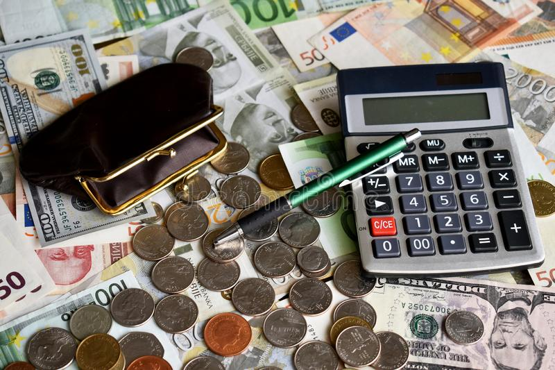 Ballpen wallet calculator and money. Money from different countries in background, wallet, calculator, ballpen and coins are on it stock photo