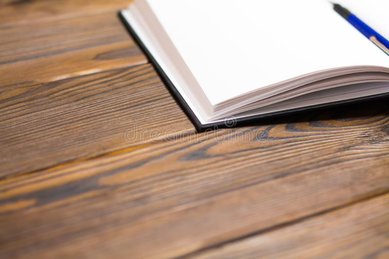 Ballpoint pen in open notebook on a dark brown wooden background. Blank pages in notebook. Concept - free writing. Ballpoint pen in a notebook on a dark brown royalty free stock images