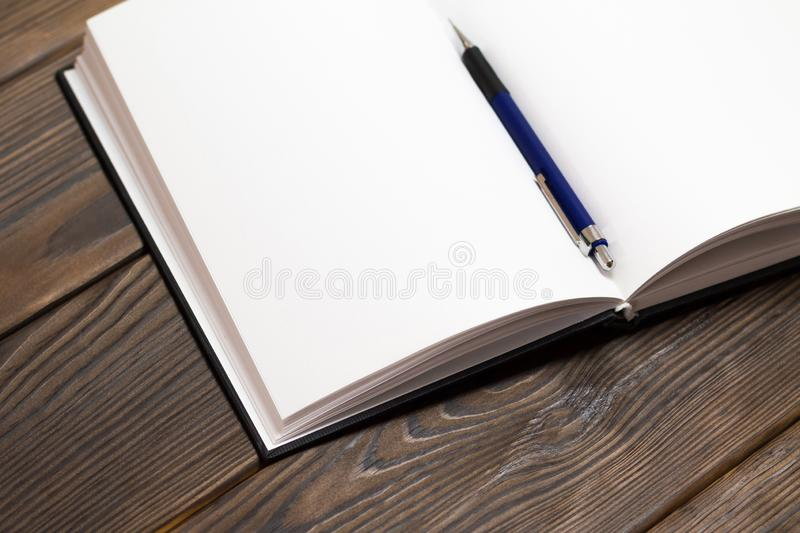Ballpoint pen in open notebook on a dark brown wooden background. Blank pages in notebook. Concept - free writing. closedup. Ballpoint pen in a notebook on a stock photo