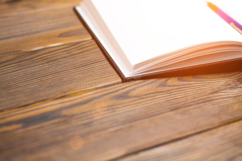 Ballpoint pen in open notebook on a dark brown wooden background. Blank pages in notebook. Concept - free writing. Toned with sunl. Ballpoint pen in a notebook royalty free stock images