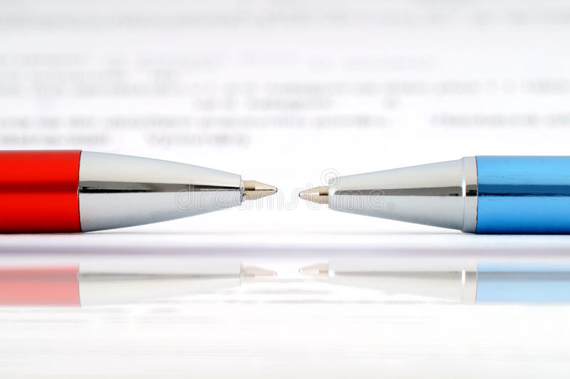 Ballpoint pens and document. Two ballpoint pens lying against each other and document royalty free stock photo