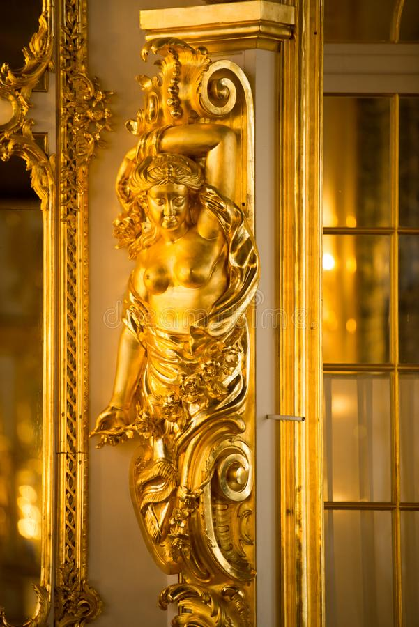 Golden statue in ballroom of roccoco palace Catherine Palace,  located in the town of Tsarskoye Selo or Pushkin St. Petersburg. Ballroom in the Catherine Palace royalty free stock image