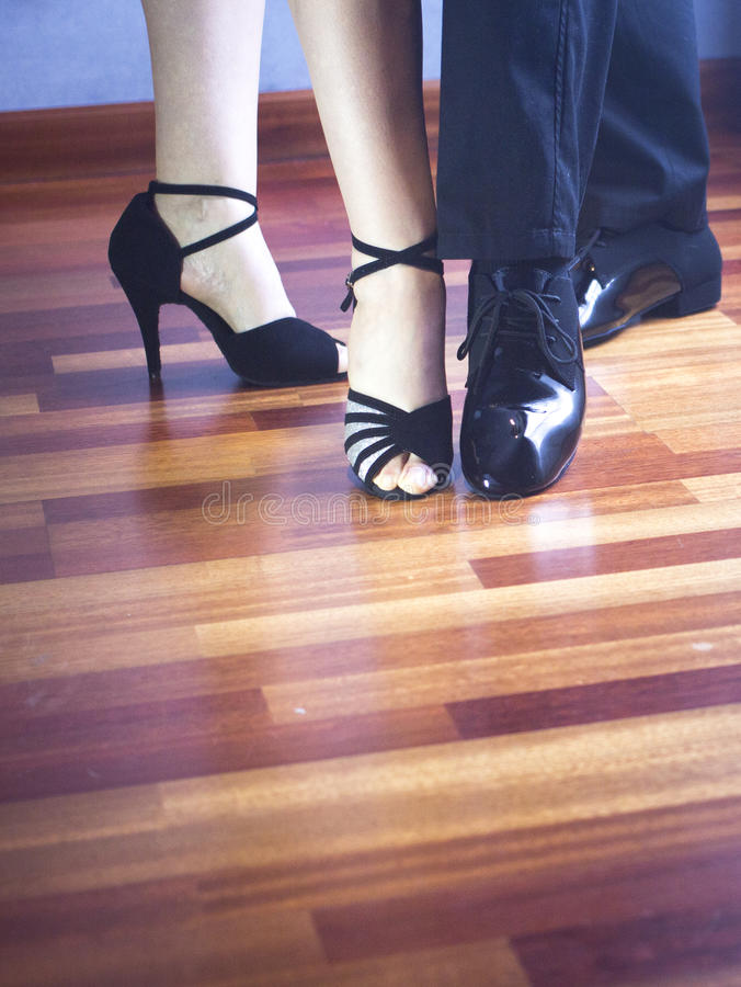 Ballroom dance latin dancers. Male and female ballroom, standard, sport dance, latin and salsa couple dancers feet and shoes in dance academy school rehearsal royalty free stock image