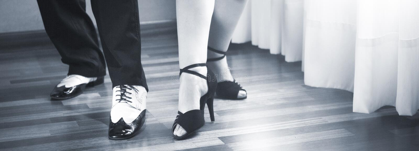 Ballroom dance latin dancers. Male and female ballroom, standard, sport dance, latin and salsa couple dancers feet and shoes in dance academy school rehearsal royalty free stock photo