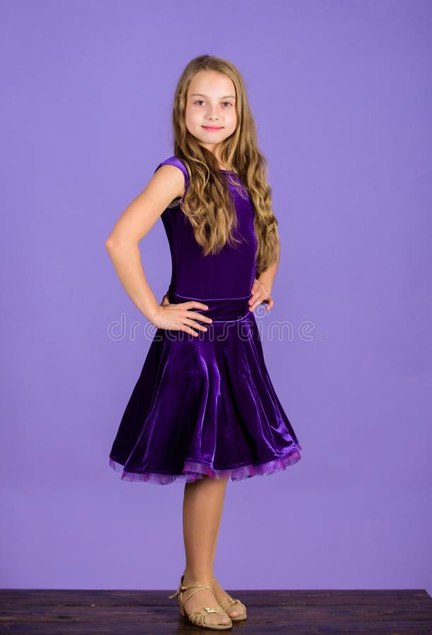 Ballroom dancewear fashion concept. Kid dancer satisfied with concert outfit. Girl cute child wear velvet violet dress. Clothes for ballroom dance. Kids stock photography