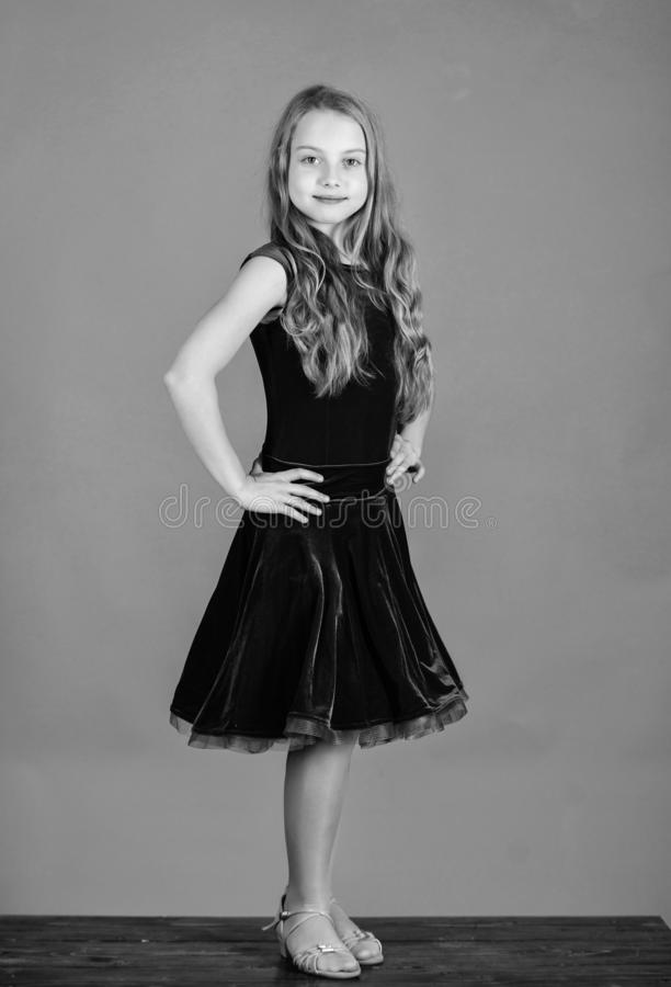 Ballroom dancewear fashion concept. Kid dancer satisfied with concert outfit. Girl cute child wear velvet violet dress. Clothes for ballroom dance. Kids stock image