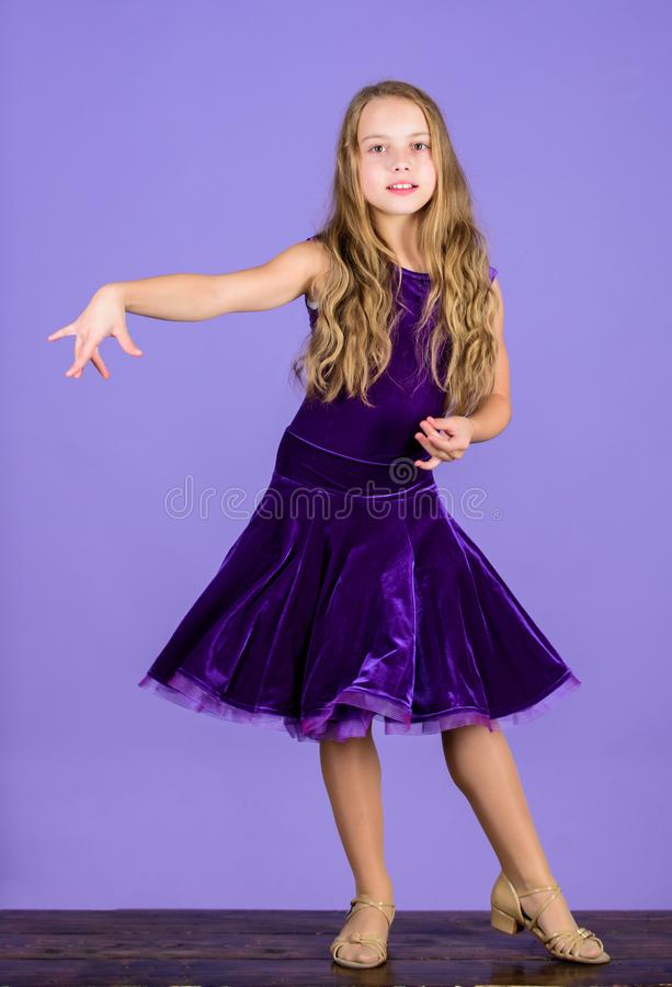 Ballroom dancewear fashion concept. Kid dancer satisfied with concert outfit. Kids fashion. Girl cute child wear velvet. Violet dress. Clothes for ballroom royalty free stock photos