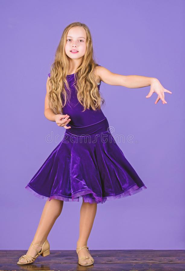 Ballroom dancewear fashion concept. Kid dancer satisfied with concert outfit. Kids fashion. Girl cute child wear velvet. Violet dress. Clothes for ballroom stock image