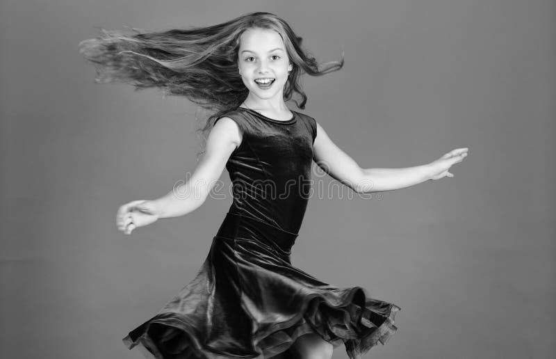 Ballroom fashion. Girl child wear velvet violet dress. Kid fashionable dress looks adorable. Ballroom dancewear fashion. Concept. Kid dancer satisfied with stock photo