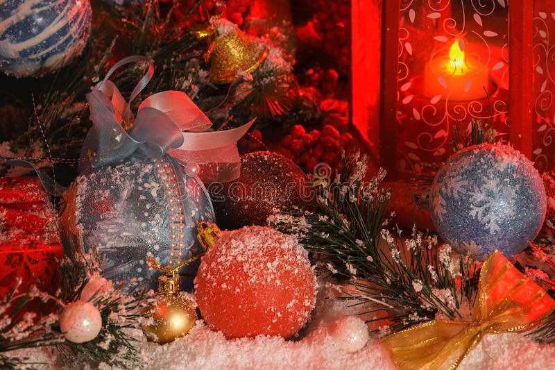 Balls and Christmas bell are covered with snow in the light of a red lantern on the background of New Year`s scenery. The magic of Christmas and New Year stock photo