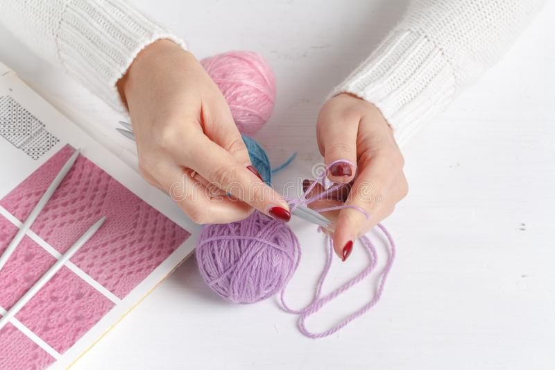 Balls of colored yarn. Sample knit. Women`s hands are knitted royalty free stock photography