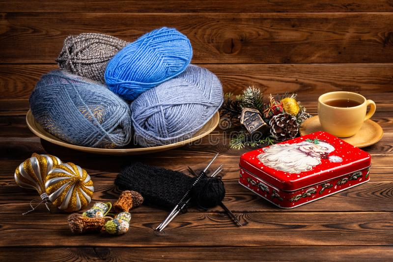 Balls of gray and blue threads in a wooden plate, Christmas decorations and a metal box with a picture of Santa Claus knitting royalty free stock photos