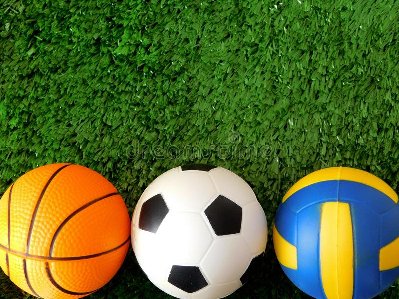 Balls for soccer, basketball and volleyball are lying on the green grass. stock photos