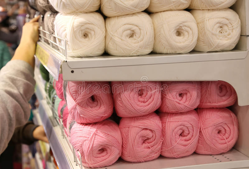 Balls of wool for sale on the shelf. Many balls of wool for sale on the shelf in the shop of importers of fabrics and wool stock photo