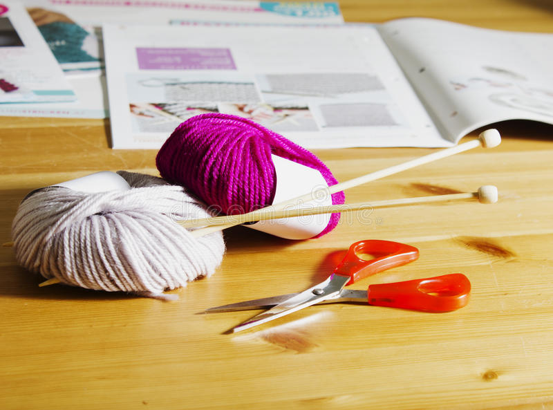 Balls of wool and wooden knitting needles on the table. stock images