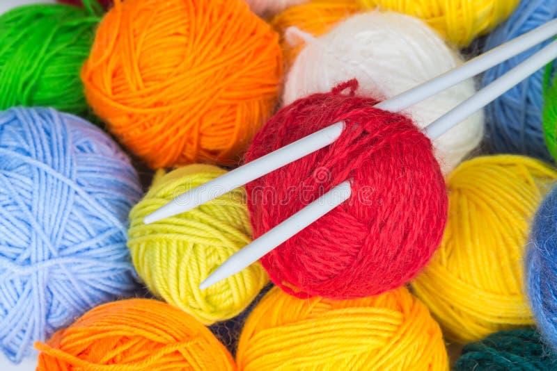 Balls of wool yarn and knitting needles. Colorful balls of wool yarn and knitting needles royalty free stock photo