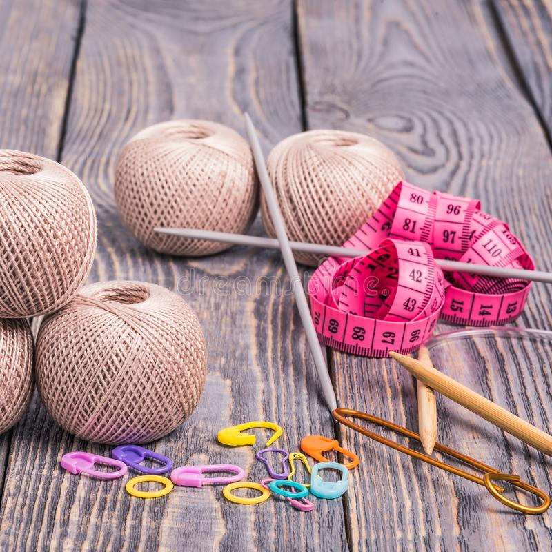 Thread clews. Balls of yarn, knitting needles, measuring tape and clips on wooden background stock image