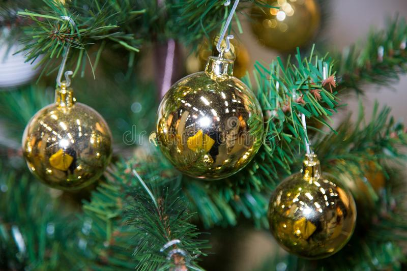 Balls yellow Christmas hanging on the branches of a green Christmas tree in the background light. Toys, New year royalty free stock image