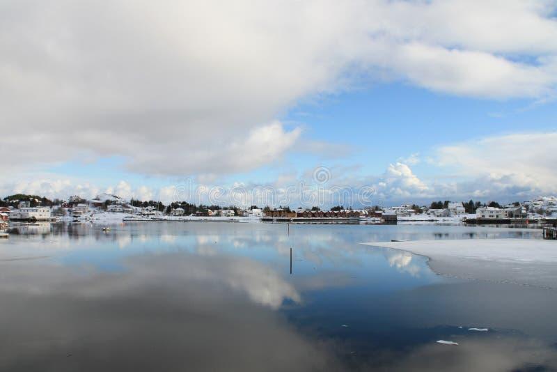 Ballstad in Lofoten mirroring. The village of Ballstad in Lofoten and the clouds mirroring in his fjrd royalty free stock photo