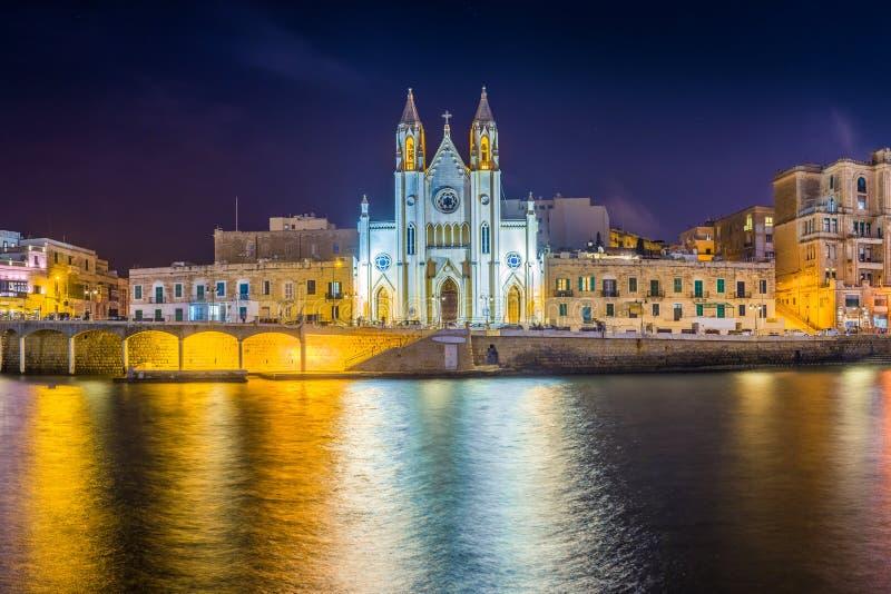 Balluta海湾,马耳他-我们的迦密山的夫人著名教会的全景Balluta海湾的在夜之前 免版税库存图片