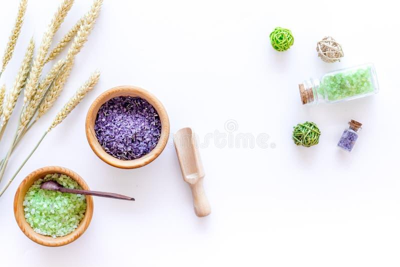 Balneario casero con la sal cosmética de las hierbas del trigo para el baño en la opinión superior del fondo blanco del escritori fotos de archivo libres de regalías