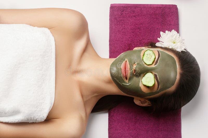 Balneario Clay Mask Mujer con la m?scara facial de la arcilla y pepinos en ojos fotos de archivo