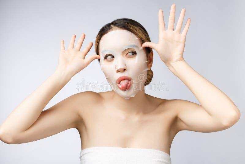 Balneario, cuidado médico Muchacha asiática con un aislante cosmético de la máscara en blanco imagen de archivo libre de regalías