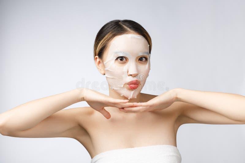 Balneario, cuidado médico Muchacha asiática con un aislante cosmético de la máscara en blanco fotografía de archivo