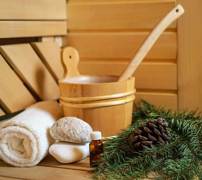 Balneario, sauna finlandesa y ajuste de la salud con el cubo de agua, esencia del aceite, conos, ramas de árbol de navidad, toall foto de archivo libre de regalías