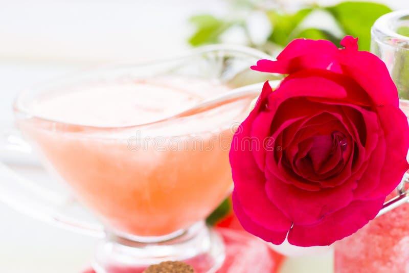 Balneario y ajuste de la salud con la flor color de rosa, sal del mar, aceite en una botella en fondo blanco de madera foto de archivo