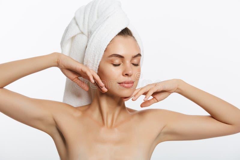 Balneario y concepto de la belleza - chica joven feliz con la piel limpia y con una toalla blanca en su cara principal de los lav fotos de archivo libres de regalías
