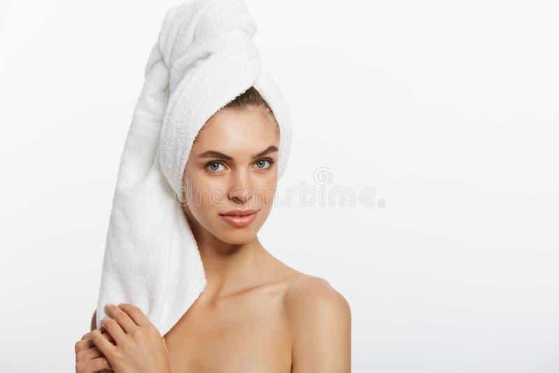 Balneario y concepto de la belleza - chica joven feliz con la piel limpia y con una toalla blanca en su cara principal de los lav fotografía de archivo