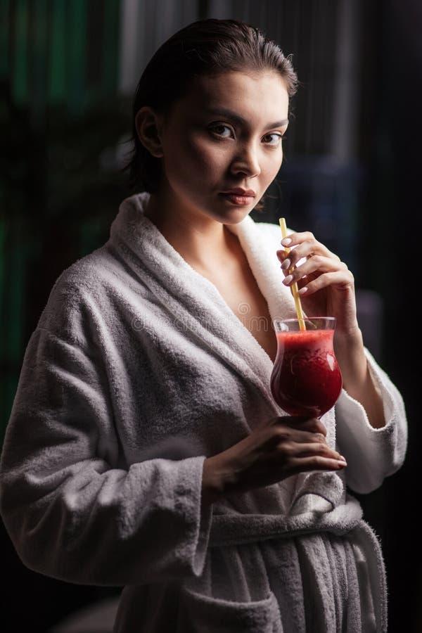 Balneario y salud Muchacha en albornoz que bebe el zumo de naranja en salón del balneario fotos de archivo libres de regalías