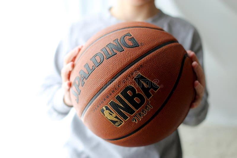 Baloncesto en las manos de un niño fotografía de archivo