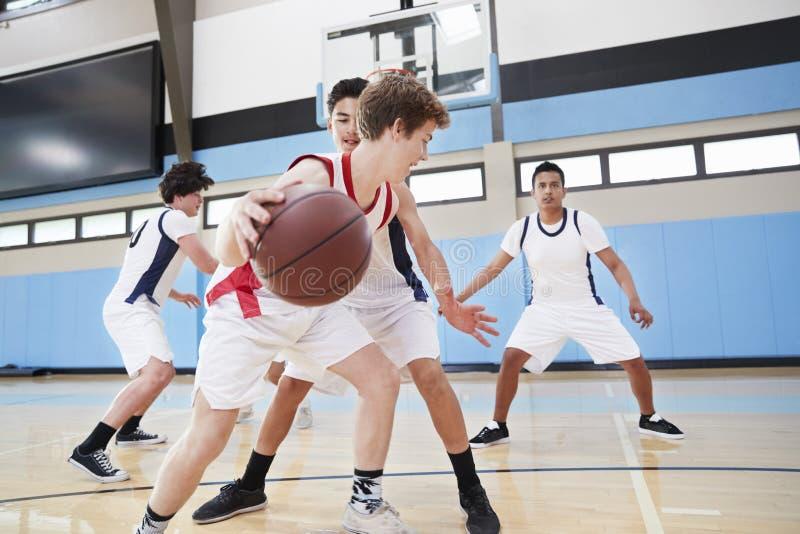 Baloncesto masculino Team Dribbling Ball On Court de la High School secundaria fotos de archivo