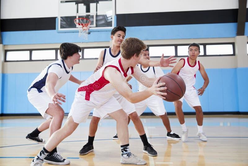 Baloncesto masculino Team Dribbling Ball On Court de la High School secundaria imágenes de archivo libres de regalías