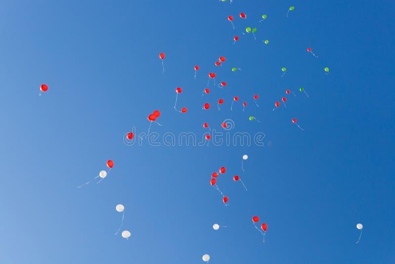 baloney Дети выпустили много шарики с веревочками в небе Красные и зеленые воздушные шары в голубом небе в лучах солнца стоковое изображение