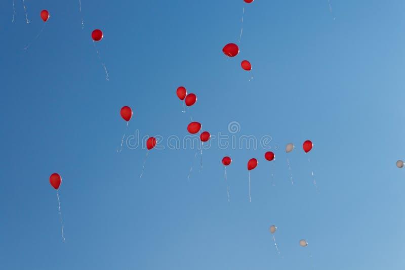 baloney Дети выпустили много шарики с веревочками в небе Красные и зеленые воздушные шары в голубом небе в лучах солнца стоковое фото rf