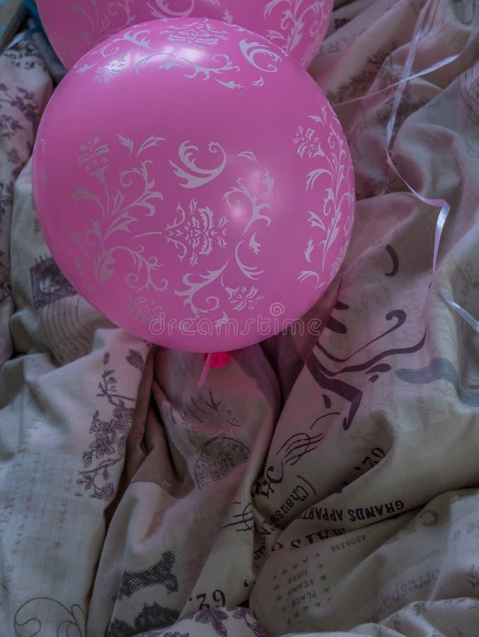 Baloon cor-de-rosa do tempo do partido em uma cama foto de stock