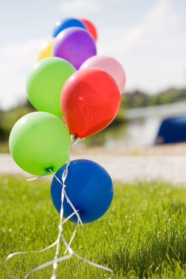 Baloons colorés d'hélium à l'herbe vis-à-vis du ciel bleu photographie stock libre de droits