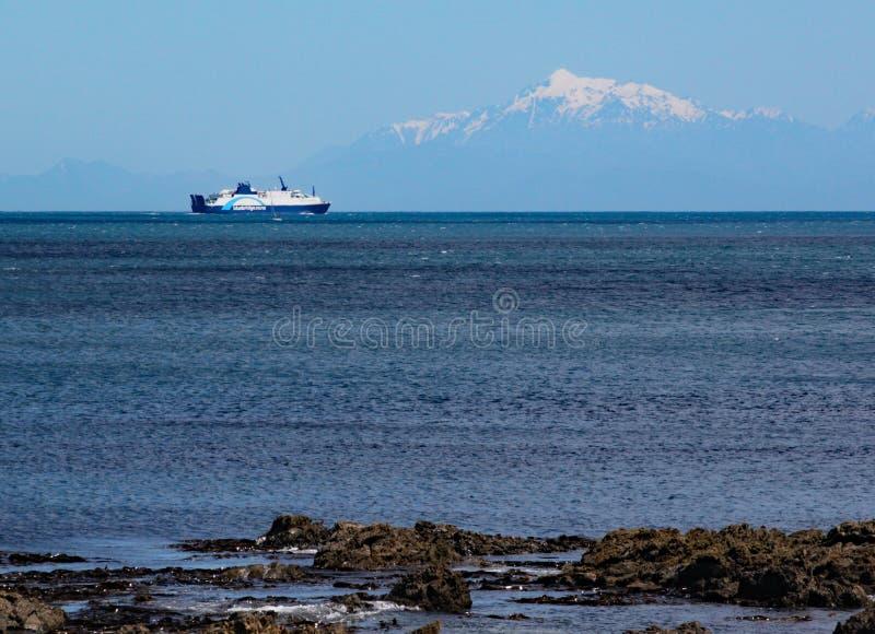 Balsa de Interislander nas velas de Strait do cozinheiro para a ilha sul A neve tampou montanhas pode ser vista no fundo imagens de stock royalty free