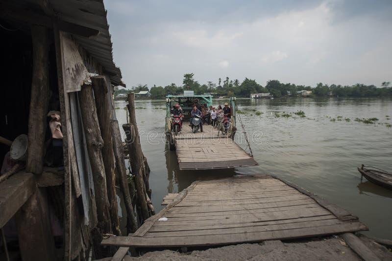 Balsa de madeira pequena velha com os começos dos passageiros do pé e das bicicletas que cruzam o Mekong River em seu delta em Vi foto de stock