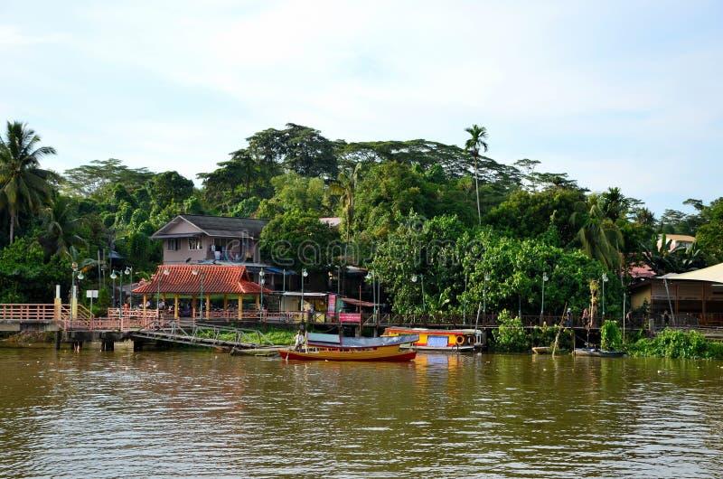 A balsa do rio com barqueiro alcança o cais do molhe da aterrissagem através do rio Kuching Malásia de Sarawak imagem de stock royalty free